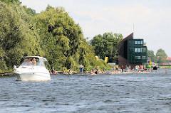 Holzstege an der Dove-Elbe, Wasserpark Allermöhe - Regattastrecke; ein Sportboot, Motorboot fährt flussabwärts Richtung Tatenberger Schleuse.
