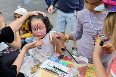 Grillfest von AnwohnerInnen und Flüchtlingen im Hamburger Karoviertel auf dem Tschaikowsky-Platz - Kinderschminken.