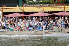 Strandperle in Hamburg Othmarschen bei Hochwasser / Flut; ein schmaler Strandstreifen bleibt für die Gäste der beliebten Gaststätte mit Blick auf den Hamburger Hafen und die vorbeifahrenden Schiffe.