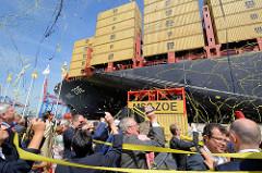 Taufe des Containerschiffs MSC ZOE im Hamburger Hafen - die Gäste fotografieren die Zeremonie / Luftschlangen fliegen um das Frachtschiff.