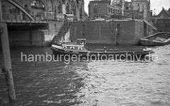Die Barkasse ANITA fährt im Magdeburger Hafen Richtung Brooktorhafen; lks. ein Ausschnitt des Eisen- bogens der Magdeburger Brücke. Vor dem Kaispeicher B steht ein LKW mit Anhänger, die Ladefläche ist mit einer Plane abgedeckt. Die Kaimauer ist du