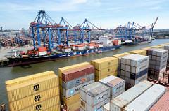 Blick über die Containerladung zum Hamburger Containerterminal Burchardkai - ein Containerschiff liegt am Kai, die Containerladung wird gelöscht.