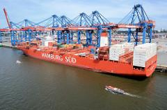 Der Containerfrachter Cap San Artemissio der Reederei Hamburg Süd unter den Containerbrücken des Hamburger Terminals Burchardkai - eine Barkasse mit Touristen auf der Fahrt durch den Hafen.