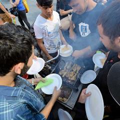 Grillfest von AnwohnerInnen und Flüchtlingen im Hamburger Karoviertel; auf einem kleinen Grill wird Fleisch gebraten.