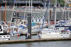 City Sportboothafen Hamburg - Motorboote und Segelboote liegen im Hamburger Stadthafen - im Hintergrund die Promenade mit Terrasse / Stufen zum Sitzen.