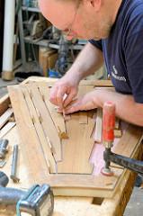 Die Bugklappe des Daysailers wird mit Massivholz-Mahagonieleisten versehen.