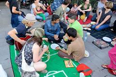Grillfest von AnwohnerInnen und Flüchtlingen im Hamburger Karoviertel. AnwohnerInnen spielen Guitarre - Kinder hören zu.