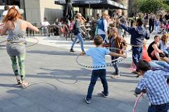 Grillfest von AnwohnerInnen und Flüchtlingen im Hamburger Karoviertel; Kinder spielen mit Hula Hoop Reifen.