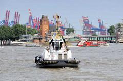 Schlepper / Hafenschlepper bei der Arbeit vor Hamburg Finkenwerder - im Hintergrund die Lotsestation und Containerkräne beim Waltershofer Hafen.