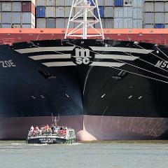Bug des Containerfrachters MSC ZOE im Hamburger Hafen - Barkasse mit Touristen auf Hafenrundfahrt.
