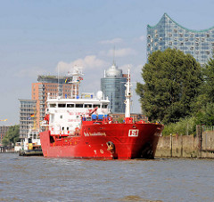Das Tankschiff Stolt Sanderling läuft in den Hamburger Hafen ein und legt am Reiherstieg an; im Hintergrund die Elbphilharmonie und Bürogebäude in der Hamburge Hafencity.