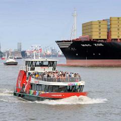 Am Schiffswendeplatz vor dem Waltershofer Hafen wird die MSC ZOE mit der Hilfe von Schleppern gedreht - im Hintergrund die Hamburger Skyline - eine Hafenfährte dicht besetzt mit Passagieren in Fahrt.