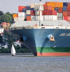 Bug des Containerschiffs MOL BREEZE auf der Elbe vor Hamburg Blankenese - ein Segelschiff kreuzt auf dem Wasser. Die MOL BREEZE wurde 2014 gebaut, hat eine Länge von 337 m und kann 10010 TEU Standardcontainer transportieren.
