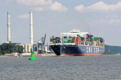 Der Containerfrachter CMA CGM Amerigo Vespucci auf der Elbe vor Wedel - am Ufer die Schornsteine und das Heizkraftwerk Wedel. Die Amerigo Vespucci hat eine Länge von 365 m und kann 13830 TEU Container transportieren.