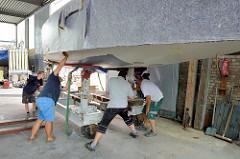 Stabilisieren vom Rumpf des Daysailers auf dem Werftwagen - Gurten werden unter dem Schiffsrumpf durchgezogen.