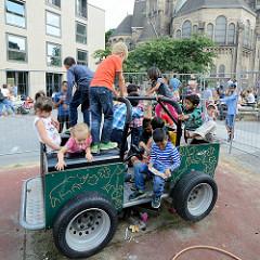 Grillfest von AnwohnerInnen und Flüchtlingen im Hamburger Karoviertel auf dem Tschaikowsky-Platz; Kinder spielen auf einem Spielzeugauto.