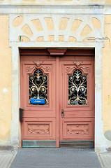 Geschnitzte Dekortür / Doppeltür mit eisernem Jugendstildekor vor den Fenstern; Dammhaststrasse von Zehdenick.