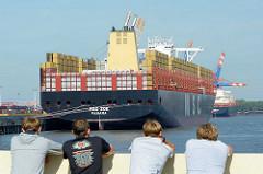Schaulustige beobachten das Frachtschiff MSC ZOE an seinem Liegeplatz im Hafen Hamburgs.