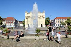 Springbrunnen am Louisenplatz in Potsdam - Blick zum Brandenburger Tor. Das wurde 1771 von Carl von Gontard und Georg Christian Unger im Auftrag Friedrichs II. gebaut.