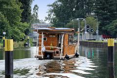 Ein Hausboot fährt auf der Havel zur Schleuse Zehdenick - die Signallichter der Schleuse zeigen Grün.