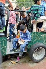 Grillfest von AnwohnerInnen und Flüchtlingen im Hamburger Karoviertel auf dem Tschaikowsky-Platz; Kinder spielen auf einem Spielzeugauto, ein Junge liest ein Bilderbuch.