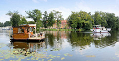 Blick über die Havel bei Zehdenick - ein Hausboot und Motorboot fahren Richtung Schleuse; im Hintergrund das Havelschloss / Restaurant, Hotel.