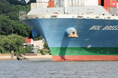 Containerfrachter MOL BREEZE auf der Elbe vor Hamburg Blankenese, Falkensteiner Ufer - ein Schiffswrack liegt am Strand.