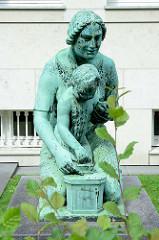 Bronzeskulptur Frau mit Kind - Spardose an der Max-Brauer-Allee - Gebäude Altonaer Spar- und Bauverein; Bildhauer O. G. Hermann Perl.