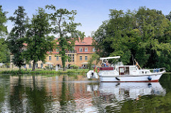 Blick über die Havel bei Zehdenick - ein Motorboot fährt Richtung Schleuse; im Hintergrund das Havelschloss / Restaurant, Hotel.