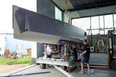Stabilisieren vom Rumpf des Daysailers auf dem Slipwagen - Tragegurte werden unter dem Schiffsrumpf durchgezogen.