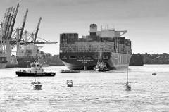 Der Containerfrachter CMA CGTM KERGUELEN läuft aus dem Hamburger Hafen aus - Motorboote und Segelboot im Waltershofer Hafen.