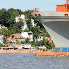 Bug des Containerschiffs META auf der Elbe vor Hamburg Oevelgoenne - am  Ufer die Strandperle und Gäste am Strand.