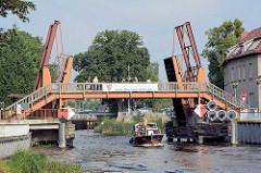 Ein Motorboot fährt auf der Havel unter der geöffneten Hastbrücke / Doppelzugklappbrücke von Zehdenick.