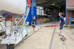 Der Rumpf vom Daysailor liegt auf dem Slipwagen - Stahlrungen werden zur Sicherung des Schiffkörpers montiert.