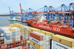 Blick über die Containerladung eines Frachtschiffs auf den Hamburger Hafen und das Container Terminal Burchardkai; ein roter Frachter der Reederei Hamburg Süd liegt am Hafenkai.