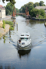 Ein Sportboot fährt auf der Havel zur Schleuse Zehdenick - im Hintergrund die geöffnete Hastbrücke, Doppelzugklappbrücke über den Fluss.