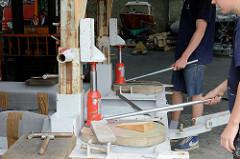 Mit hydraulischen Wagenhebern wird der Schiffsrumpf gleichmässig auf dem Slipwagen angehoben.