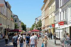 Fussgängerzone Brandenburger Strasse in Potsdam - Touristen schlendern in der Sonne, Strassencafés und Restaurants - im Hintergrund das historische Brandenburger Tor.