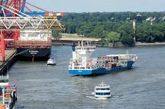 Schiffsverkehr im Waltershofer Hafen von Hamburg - ein Container Carrier, Container Feeder läuft aus dem Hafenbecken aus - zwei Fahrgastschiffe mit Touristen fahren durch den Hafen.