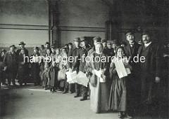Männer, Frauen, Kinder stehen mit ihren Papieren im Empfangsgebäude der Auswandererhallen zur Registrierung Schlange.