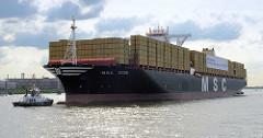 Der Frachter MSC ZOE bei seiner Jungfernfahrt auf der Elbe bei Hamburg - ein Schlepper unterstützt das Riesenschiff beim Steuern.