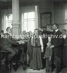 Untersuchung der AuswandererInnen in den Hamburger Auswandererhallen - einer Frau in Tracht wird ihre Größe gemessen.