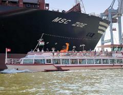 Hafenrundfahrt im Hamburger Hafen - eine Barkasse passiert im Waltershofer Hafen den hohen Bug des Containerfrachtes MSC ZOE - Touristen fotografieren das riesige Schiff.