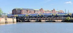 Blick vom Ericusgraben zur Oberhafenbrücke und dem Kontorhaus Fruchthof Hamburg in Hammerbrook - ein Zug der Metronom überquert die Brücke über den Oberhafenkanal.