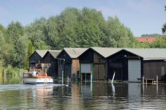 Bootshäuser an der Havel bei Zehdenick - ein Sportboot fährt in den Hafen ein.