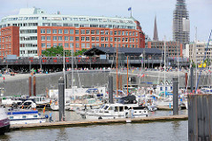 Blick über den Hamburger Sportboothafen - Marina im Stadtteil Neustadt; ein Hochbahnzug fährt in die Station Baumwall ein - der Kirchturm der St. Nikolaikirche ist eingerüstet.