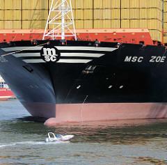 Bug mit Containerladung der MSC ZOE im Hamburger Hafen - kleines Sportboot in Fahrt.
