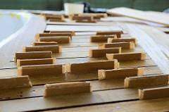 Das Mahagoniedeck des Daysailers wird angefertigt - mit Klötzchen als Abstandshalter wird die Fuge für die Verfüllung / Verfugung mit Sikaflex vorbereitet.