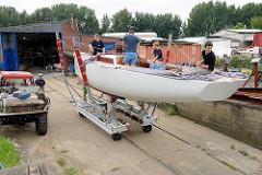 Der Daysailer Lütje 35 wird auf dem grossen Slipwagen auf der Slipanlage der Yachtwerft probeweise zu Wasser gelassen.