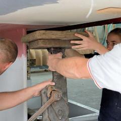 Stabilisieren vom Rumpf des Daysailers auf dem Slipwagen; mit einem  Wagenheber und Holzunterlagen wird der Schiffsrumpf abgestützt.